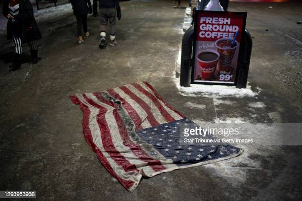 Flag was left on the pavement after the vigil and march.Community members gathered at the Holiday gas station near E. 36th St. And Cedar Ave. S....