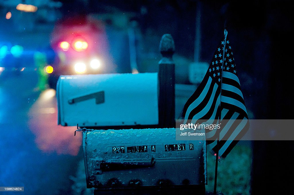 A flag waves from a mailbox as Blair County Sheriffs Deputies stand at the road block in Blair County on December 21, 2012 in Frankstown Township, Pennsylvania. According to reports, a man shot and killed two men and one woman and injured three state troopers before being shot and killed by police along Juniata Valley Road in Frankstown Township.