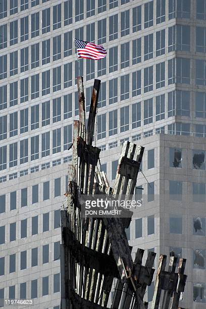 A US flag waves in the wind attached to the top of rubble at the site of the World Trade Center 23 September 2001 in New York Rescue efforts continue...