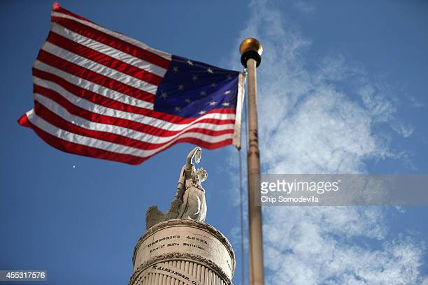 S flag with 15 stripes and 15 stars like the one that was flown Fort McHenry during the War of 1812 frames the Battle Monument during the Star...