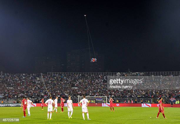 A flag with Albanian national symbols attached to a remotely operated drone flies in the stadium during brawl between players on the pitch during the...