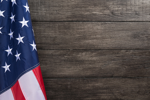 US flag with embossed stars, hanged against old wooden wall background 1177174481