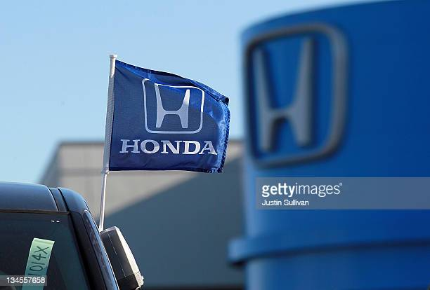 A flag with the Honda logo is displayed on brand new Honda car at Marin Honda on December 2 2011 in San Rafael California Honda Motor Co announced...