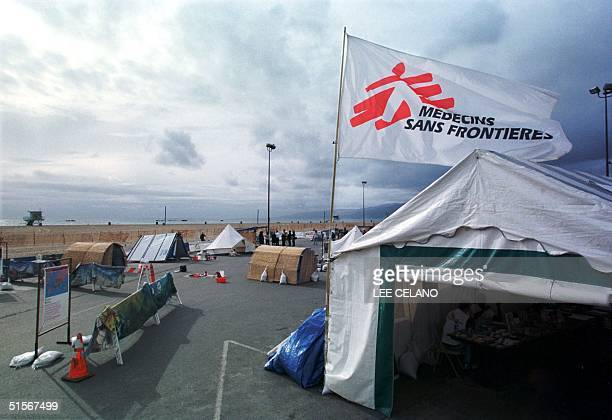 A flag with the logo of Medecins Sans Frontier an international humanitarian aid organisation flies over a mock refugee camp set up along the...