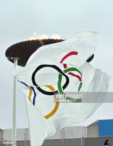 A flag with the Olympic Rings flaps in the wind below the Olympic flame that dominates the Olympic sites as weather conditions deteriorated over...