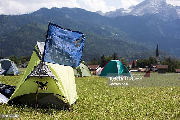 A flag with the symbol of a dove of peace flies in front of a tent where activists who have come to protest against the nearby upcoming summit of G7...