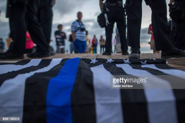 A flag with the thin blue line which is used to honor the fallen and the courage of police officers lies on the boardwalk near the feet of police...