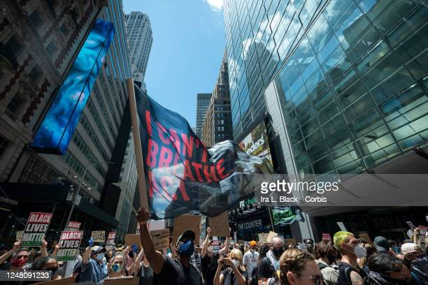 A flag with the words I Can't Breathe Act is among the thousands of protesters wearing masks and holding signs that have crowded into Times Square to...