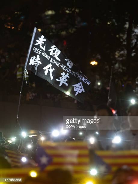 A flag with words Free Hong Kong Revolution Now waving along with Catalonia place cards during the demonstration Hundreds of masked protesters...