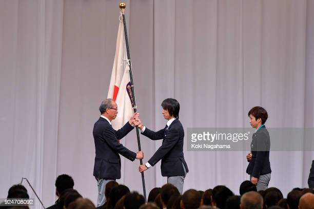 Flagbearer Noriaki Kasai and Captain of the Japanese delegations Nao Kodaira return the Japanese flag to Chef de Mission Yasuo Saito during the...