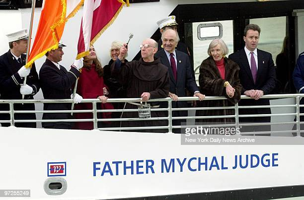 Flagbearers look on as the Rev Patrick Fitzgerald with a container of holy water blesses a NY Waterway highspeed ferry named for Father Mychal Judge...