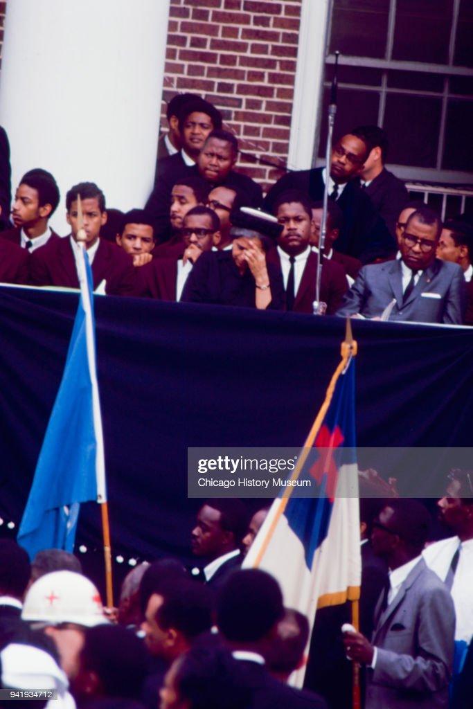 Flagbearers pass American Civil Rights activist Rosa Parks (1913 - 2005) (with hand on head), among other mourners and students, during Dr Martin Luther King Jr's public memorial service at Morehouse College, Atlanta, Georgia, April 9, 1968.