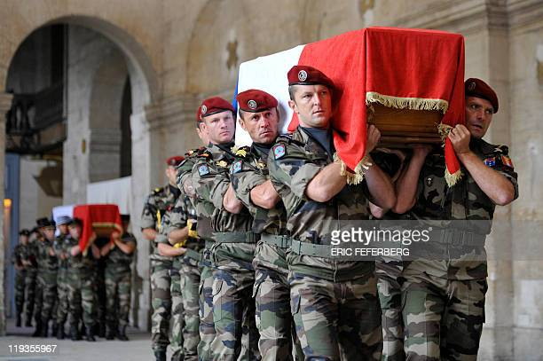 Flagdraped coffins are carried inside the SaintLouisdes Invalides chapel as France pays tribute to the seven soldiers killed last week in Afghanistan...