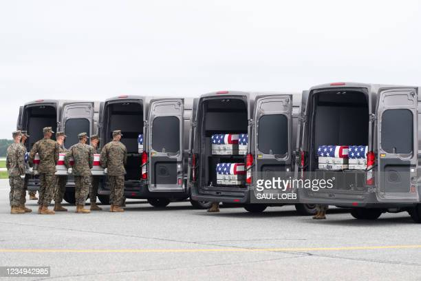 Flag-draped transfer case with the remains of a fallen service member are placed inside a transfer vehicle as US President Joe Biden attends the...
