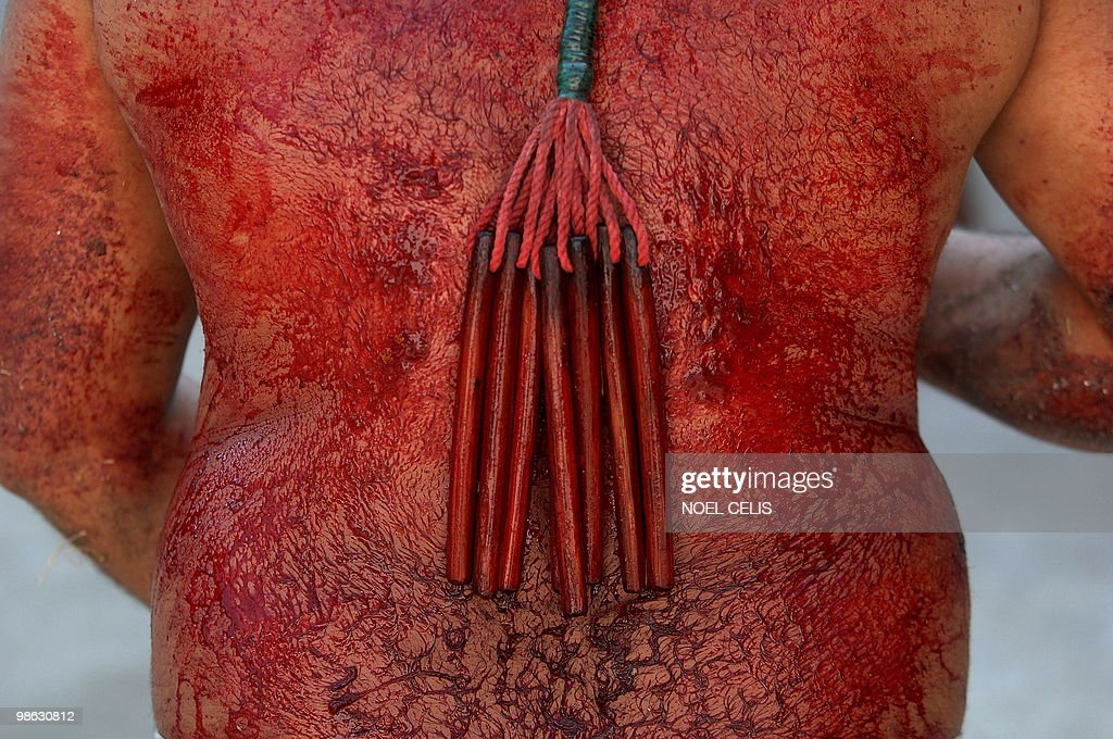 A flagellant whips his bloody back with : Nieuwsfoto's