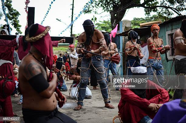 Flagellants whips their backs with wooden flails as a form of penance during holy week on April 17 2014 in Pampanga Philippines Although the act of...
