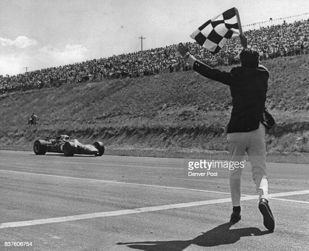 USAC flagman Shim Malone gets ready to wave checkered flag for AJ Foyt as he approaches finish line of Rocky Mountain 150mile Road Race at...