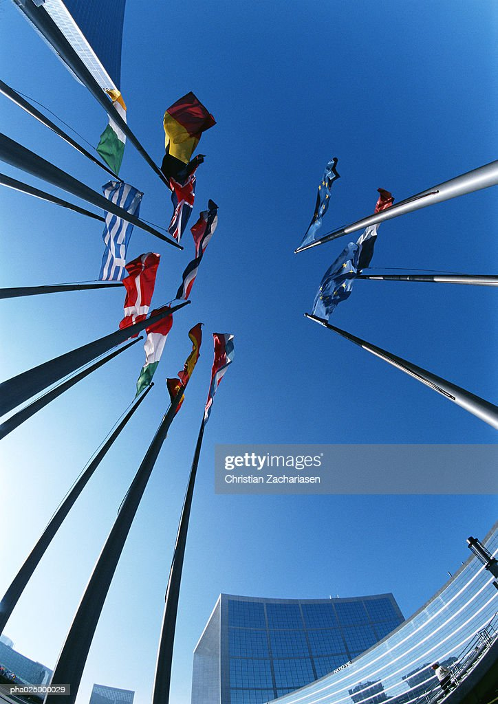 Flagpoles with flags from different countries, buildings in background, low angle shot : Stockfoto