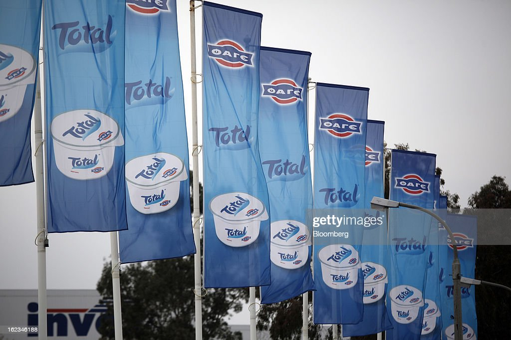 Flags advertising Total Greek yoghurt stand on display outside the Fage Dairy Industry SA plant in Athens, Greece, on Thursday, Feb. 21, 2013. An October restructuring that placed Fage International SA's Greek units in a subsidiary called Fage Dairy Industry SA coincided with Coca-Cola Hellenic Bottling SA's plan to flee the epicenter of Europe's debt crisis by moving its main stock listing to London from Athens. Photographer: Kostas Tsironis/Bloomberg via Getty Images