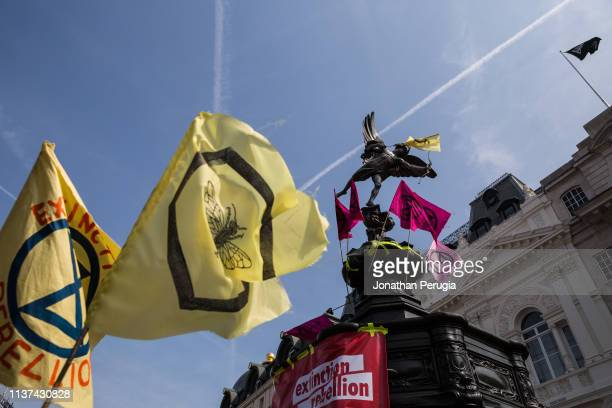 Flags and banners adorn the statue of Eros during a protest against climate change in the middle of Piccadilly Circus on 15th April 2019 in London...