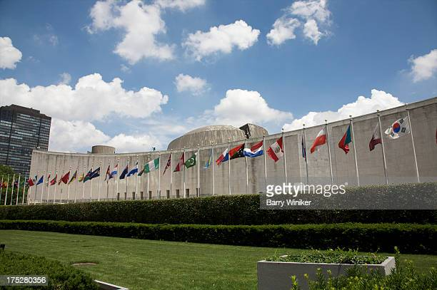 Flags and concrete building above grass and shrubs