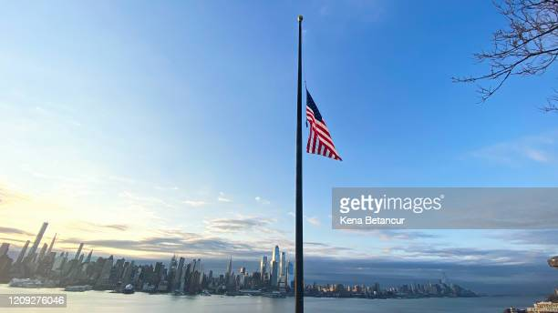 Flags are flying at half-mast as the sun rises behind in Manhattan on April 6, 2020 as seen from Weehawken, New Jersey. The U.S. COVID-19 death toll...