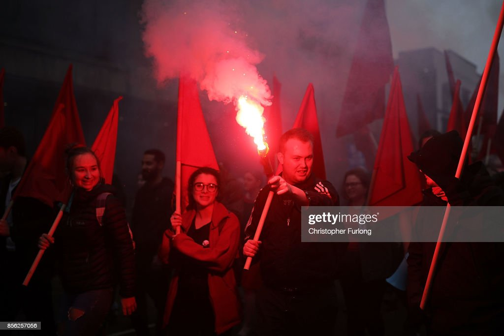 Flags are held up along with red flares as people take part in anti-Brexit and anti-austerity protests as the Conservative party annual conference gets underway at Manchester Central on October 1, 2017 in Manchester, England. Five-hundred thousand people are expected to take part in the protests with police mounting an unprecedented security operation of a thousand officers and extra armed police to protect Conservative party conference delegates.