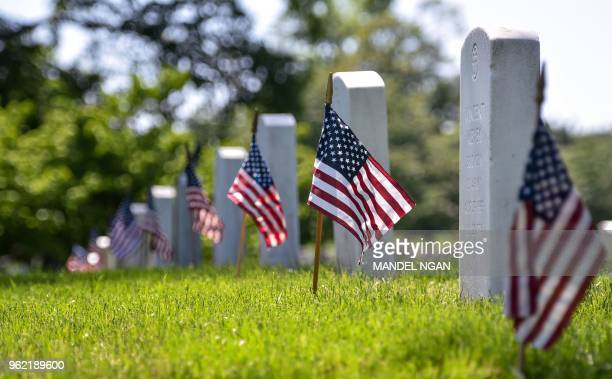 US flags are placed at graves by members of the Old Guard are seen at Arlington National Cemetery on May 24 2018 ahead of Memorial Day in Arlington...