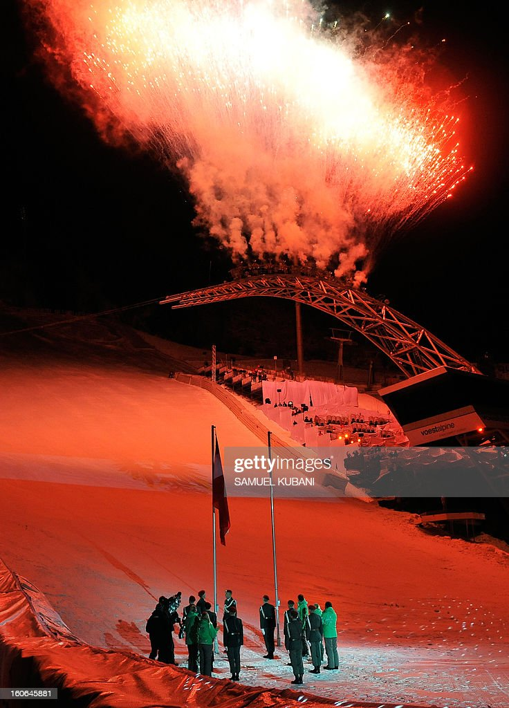 Flags are raised as fireworks illuminate the sky during the opening ceremony of the FIS World Ski Championships on February 4, 2013 in Schladming.