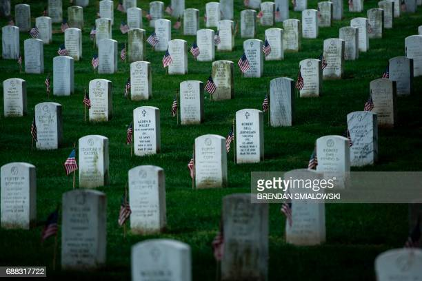 Flags are seen at graves in Arlington National Cemetery during 'Flags In' in preparation for Memorial Day May 25 2017 in Arlington Virginia / AFP...