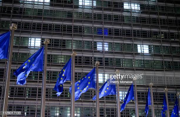 EU flags are seen in front of the Berlaymont building where people are working at night on March 6 2019 in Brussels Belgium The Berlaymont Building...