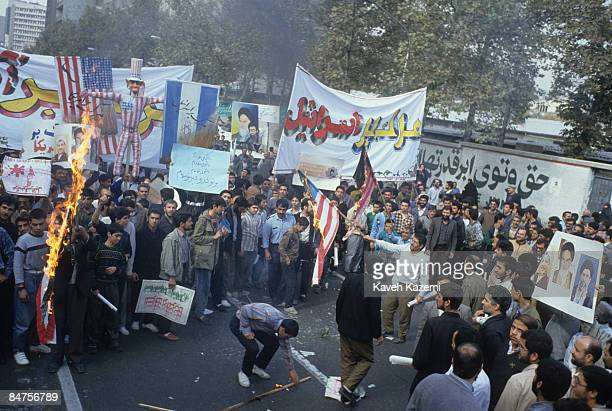 US flags are set on fire during a demonstration held outside the former American embassy in Tehran on the 16th anniversary of its occupation by...