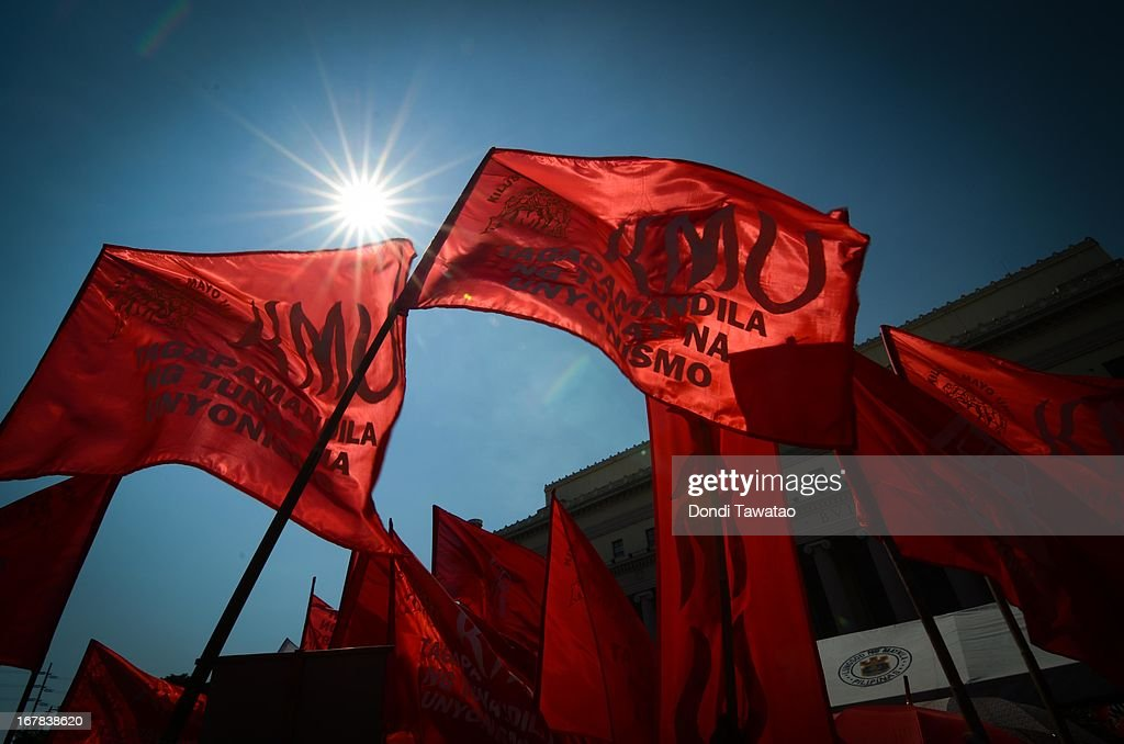 Flags are silhouetted as labor groups and trade unions march near the presidential palace on May 1, 2013 in Manila, Philippines. Philippine workers unions gather in the streets of Manila to demand, among other things, better pay, an end to contractualization and lower prices of basic commodities. Labor day is celebrated across South East Asia on May 1st and is seen as an opportunity to acknowledge the social and economic accomplishments of the workers.