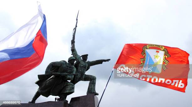 Flags are waving in front of the Soldier and Sailor monument as teenagers stand by it during celebrations in Sevastopol on March 18 to mark one year...