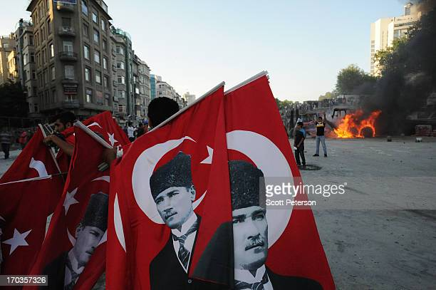 Flags bearing the image of Mustafa Kemal Ataturk are carried near a burning bulldozer as Turkish police battle antigovernment protestors as they try...