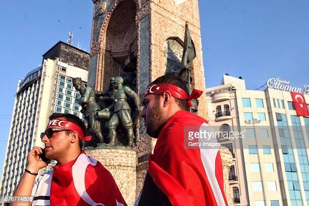 Flags covered supporters of Turkish President Recep Tayyip Erdogan stand in front of a statue of Mustafa Kemal Ataturk founder of modern Turkey with...