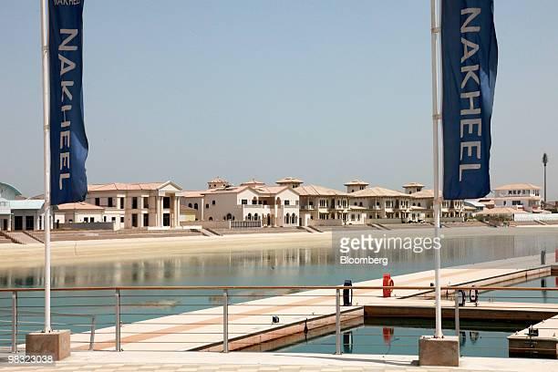 Flags displaying Nakheel branding fly near the Marina Harbor development on Dubai World's Palm Jumeirah island in Dubai, United Arab Emirates, on...