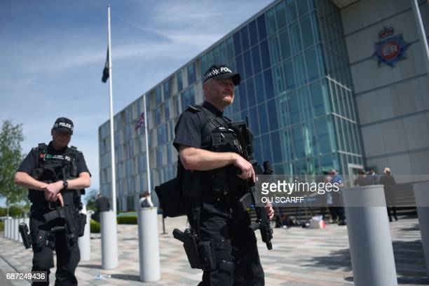 Flags fly at halfmast as armed British Police officers walk on patrol with their weapons outside of Greater Manchester Police force's headquarters in...