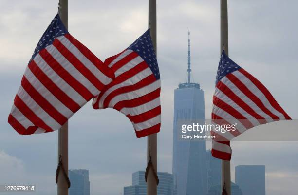 Flags fly at half-mast honoring Justice Ruth Bader Ginsberg in front of the skyline of lower Manhattan and One World Trade Center in New York City on...