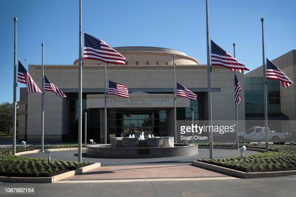 Flags fly at halfmast in front of the George HW Bush Presidential Library Center on the campus of Texas AM University on December 2 2018 in College...