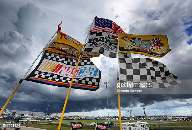 Flags fly in the infield as, for the second consecutive day, thunderstorms roll over Daytona International Speedway as Sprint Cup racing teams...