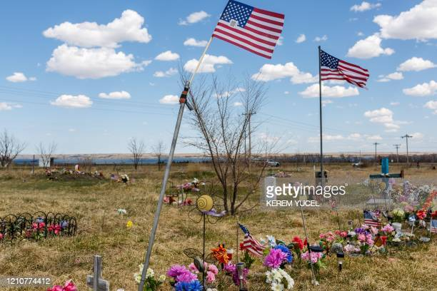 US flags fly near graves at the Lower Brule Indian Reservation on April 22 2020 in Lower Brule South Dakota The threat posed by the novel coronavirus...