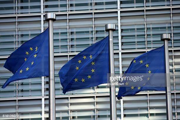 EU flags fly outside the European Commission headquarters building ahead of the EUTurkey Summit which starts today on March 17 2016 in Brussels...
