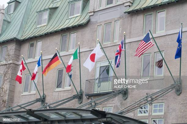 Flags fly over the Fairmont Le Manoir Richelie hotel the location for the G7 summit in La Malbaie Quebec on June 1 2018 Brewing trade tensions among...
