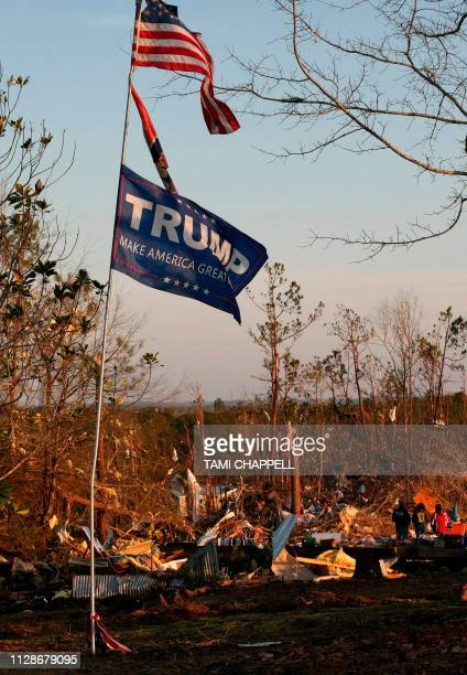 Flags fly over whats left of homes as residents clean up following a tornado that struck in Beauregard Alabama on March 4 2019 Rescuers in Alabama...
