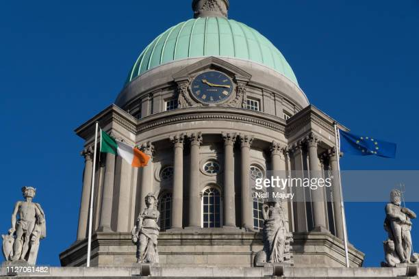 flags flying at the foot of the neoclassical dome of the custom house, dublin - irish flag stock pictures, royalty-free photos & images