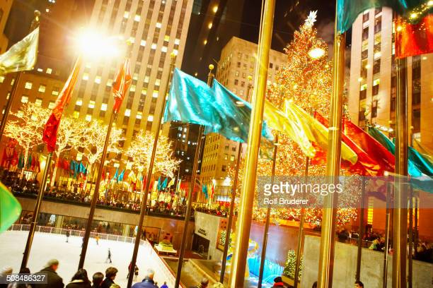 Flags flying over Rockefeller Center at night, New York, New York, United States