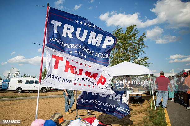 Flags for Republican presidential candidate Donald Trump fly marking the beginning of the line for his rally at Windham High School on August 6 2016...