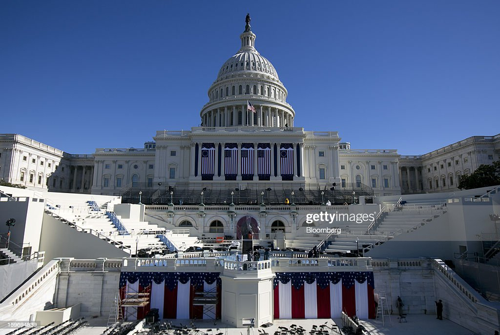 Flags hang from the U.S. Capitol prior to the second inauguration of U.S. President Barack Obama in Washington, D.C., U.S., on Friday, Jan. 18, 2013. President Obama's second inauguration next week will combine the star power of Beyonce, Kelly Clarkson and James Taylor with a lineup that reflects social values Obama will champion in his new term. Photographer: Andrew Harrer/Bloomberg via Getty Images