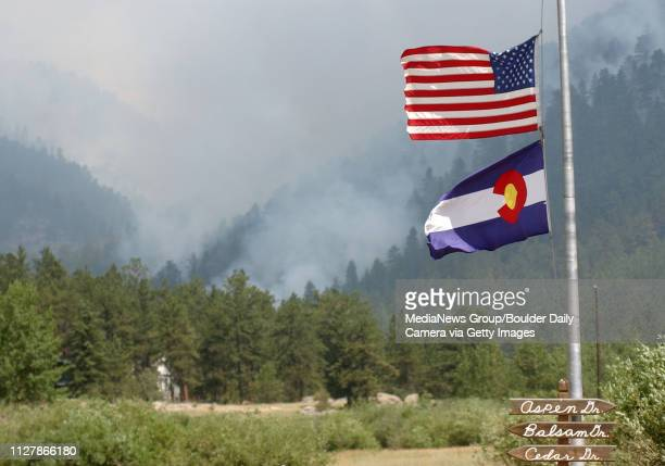 Flags in Big Elk Meadows are at half mast for the fallen air tanker pilots. The fire smokes in the valley in the background on Sunday.